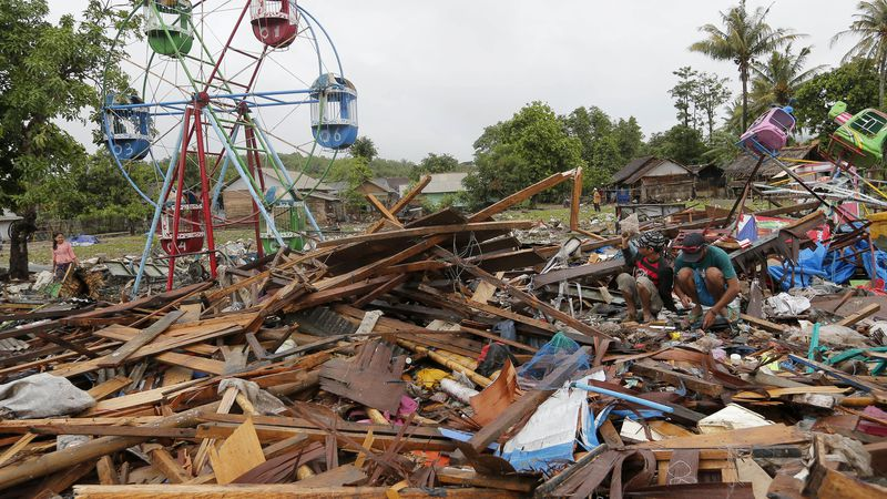 People collect usable items in debris, following Saturday's tsunami in Sumur, Indonesia,...