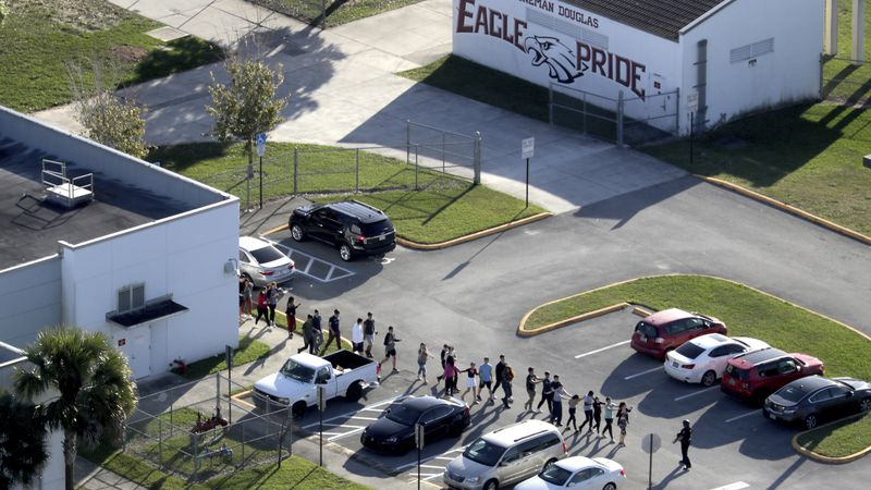 In this Feb. 14 file photo. students are evacuated by police from Marjory Stoneman Douglas High...