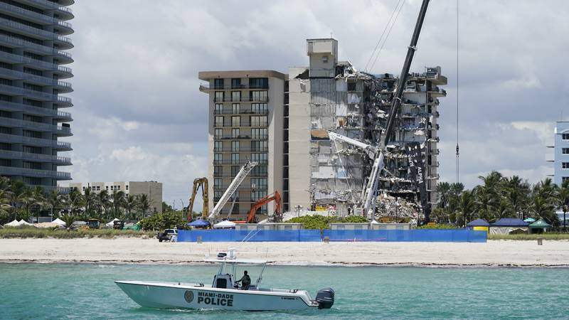 A Miami-Dade County Police boat patrols in front of the Champlain Towers South condo building,...